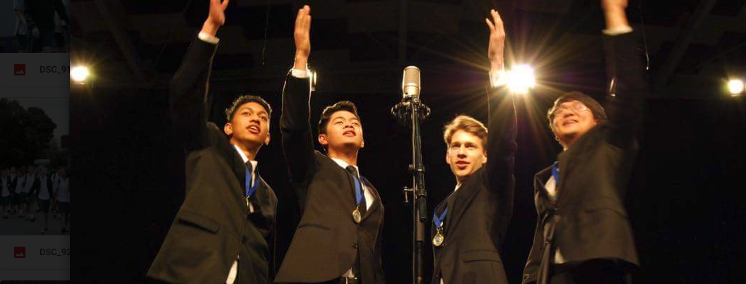 Four males with one arm raised, in black suits, singing into a shared mirophone