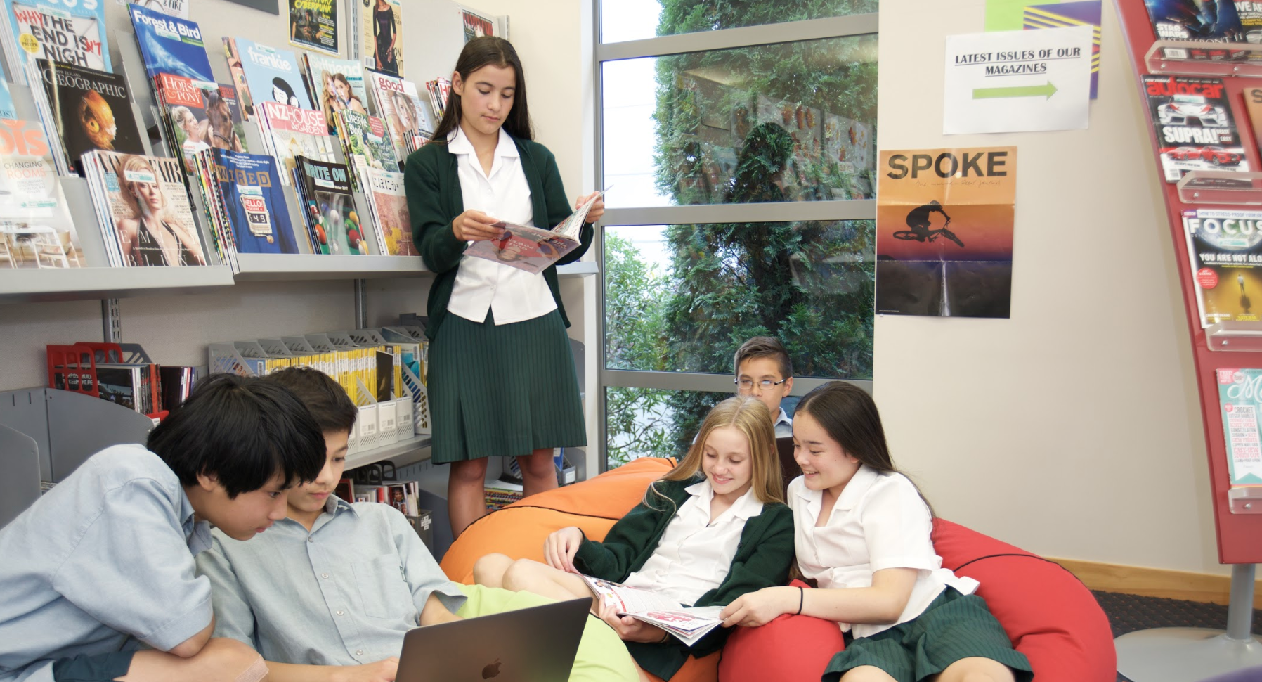 Six Burnside High School students reading books on beanbags in a library