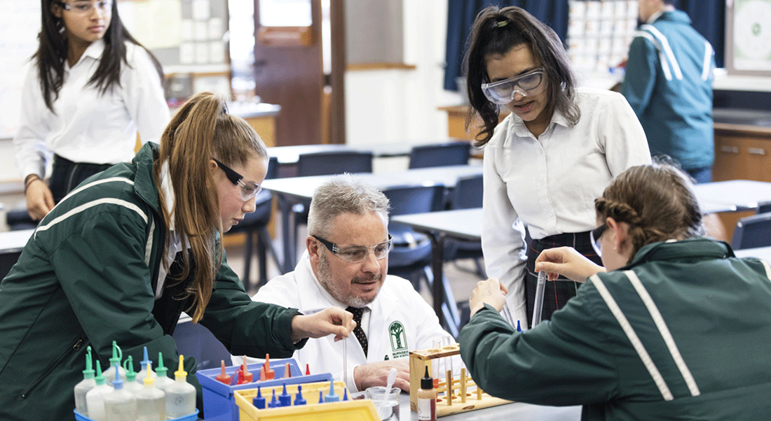 four science students and teacher with safety glasses and test tubes in a science lab