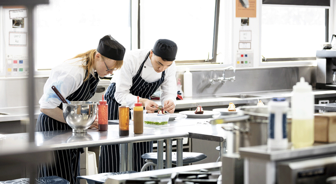 two chefs preparing food in a large kitchen